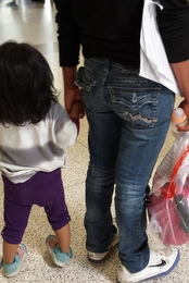 A mom and daughter wait in line at a bus station.